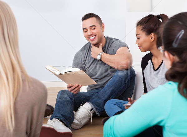 Stock photo: Group of college students reading book on floor