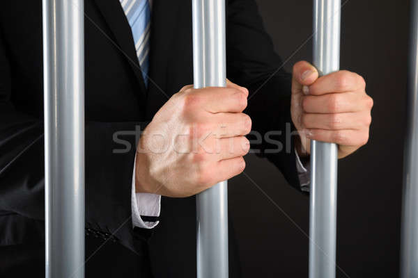 Close-up Of Businessman Holding Bars In Jail Stock photo © AndreyPopov