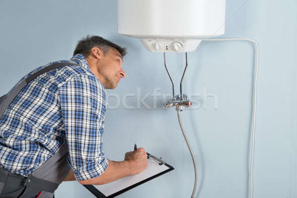 Plumber With Clipboard Looking At Electric Boiler Stock photo © AndreyPopov
