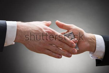 Businessman Hand Giving Bribe Stock photo © AndreyPopov