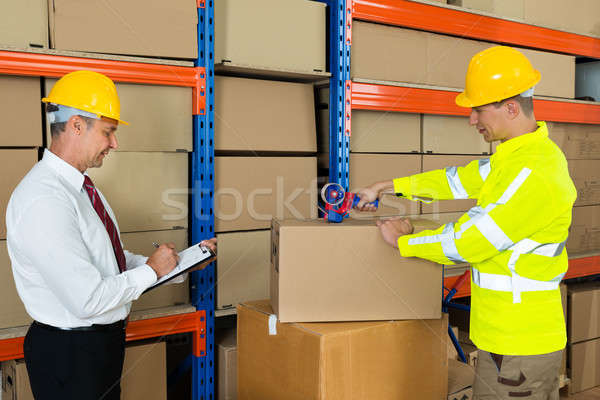 Manager With Clipboard And Worker Taping Box Stock photo © AndreyPopov