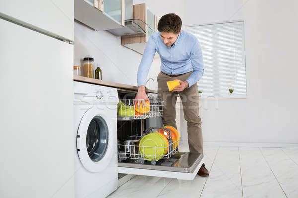 Man Putting Dishes In Dishwasher Stock photo © AndreyPopov
