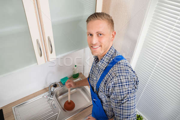 Plumber With Plunger In Kitchen Stock photo © AndreyPopov