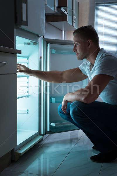 Człowiek posiedzenia pusty lodówka młody człowiek pokój Zdjęcia stock © AndreyPopov