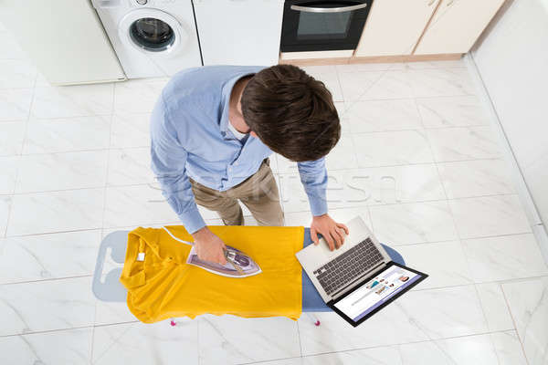 Man laptop strijken tshirt jonge man Stockfoto © AndreyPopov