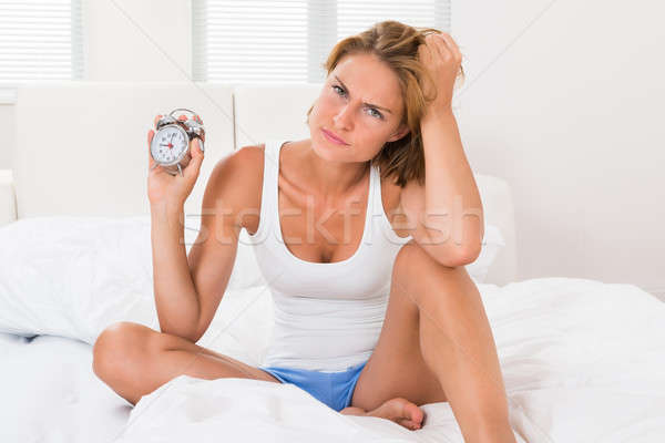 Woman Sitting On Bed With Alarm Clock Stock photo © AndreyPopov