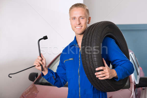 Smiling Mechanic Holding Tire And Wrench Stock photo © AndreyPopov
