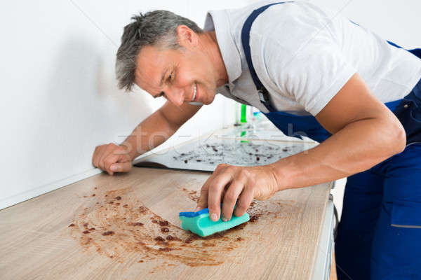 Happy Man Cleaning Counter With Sponge Stock photo © AndreyPopov