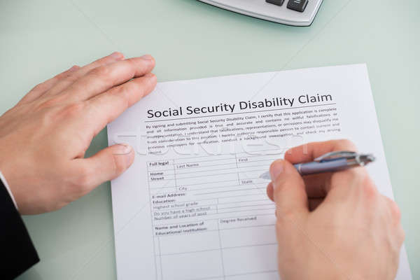 Person Hand Over Social Security Disability Claim Form Stock photo © AndreyPopov