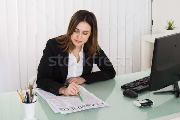 Businesswoman Reading Classifieds On Newspaper Stock photo © AndreyPopov