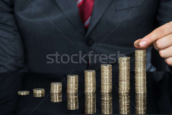 Close-up Of Businessman Hand Put Coins On Stack Of Coins Stock photo © AndreyPopov