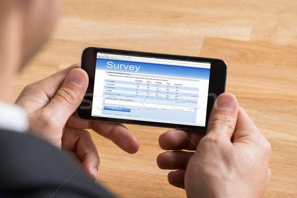 бизнесмен заполнение онлайн обзор мобильного телефона Сток-фото © AndreyPopov