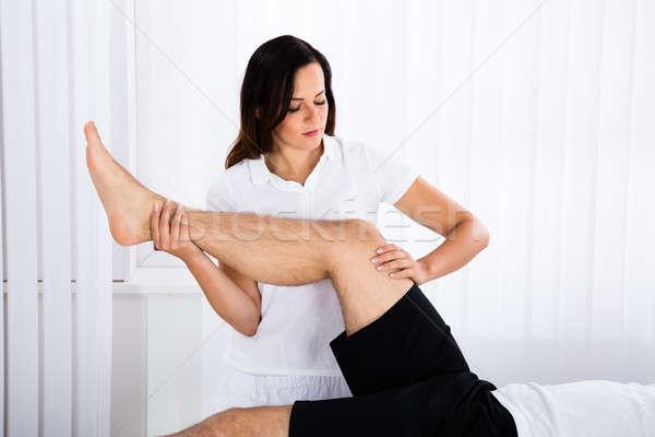 молодые женщины массажист ногу массаж человека Сток-фото © AndreyPopov