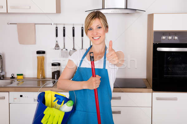 Housemaid Showing Thumbs Up In Kitchen Stock photo © AndreyPopov