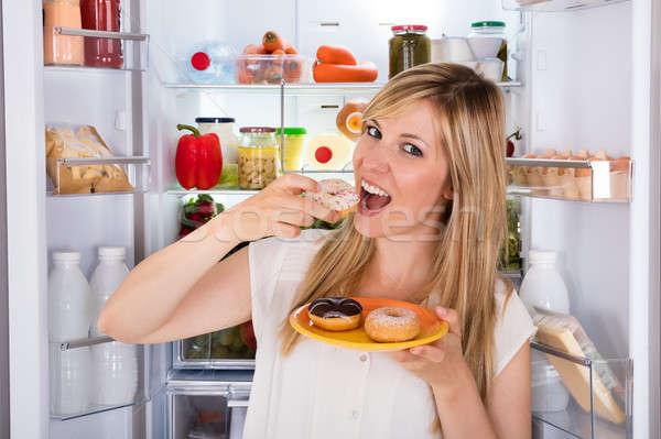 Femme manger sweet donut réfrigérateur jeunes Photo stock © AndreyPopov
