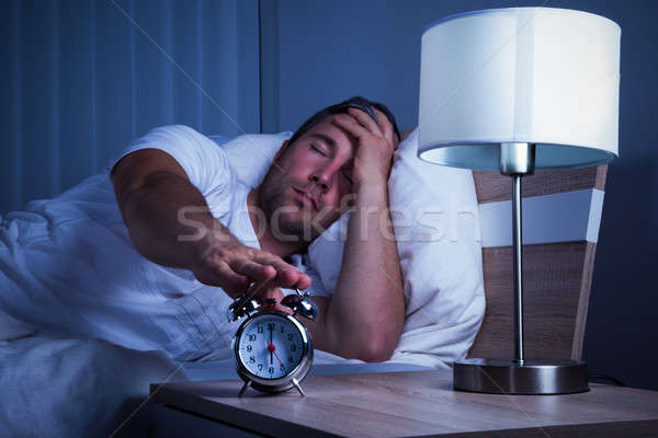 Man Turning Off The Alarm Clock Stock photo © AndreyPopov