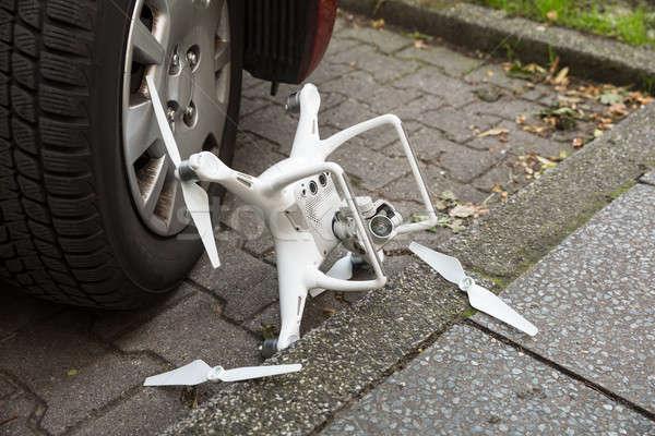 Broken drone by car wheel on footpath Stock photo © AndreyPopov