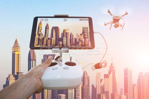 Hand controlling drone filming cityscape during sunset Stock photo © AndreyPopov