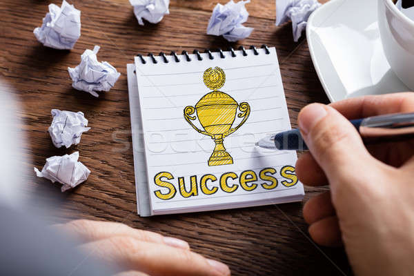 Person Drawing Trophy In Notepad Stock photo © AndreyPopov