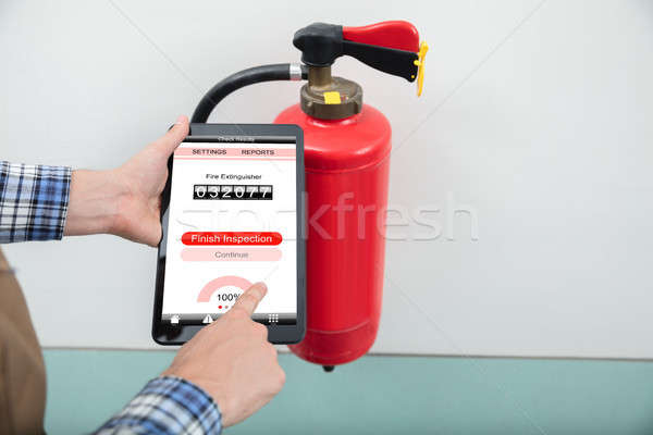 Technician Using Digital Tablet To Check Fire Extinguisher Stock photo © AndreyPopov