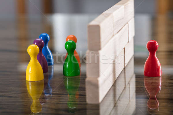Stock photo: Red And Blue Figurine Paw Separated By Wooden Blocks