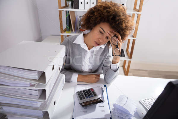 Tired Businesswoman Sitting In Office With Stack Of Files Stock photo © AndreyPopov
