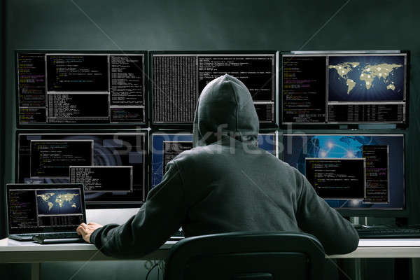 Stock photo: Hacker Using Multiple Computers For Stealing Data