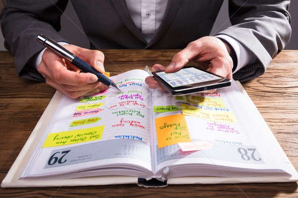 Businessperson Writing Schedule In Diary Stock photo © AndreyPopov