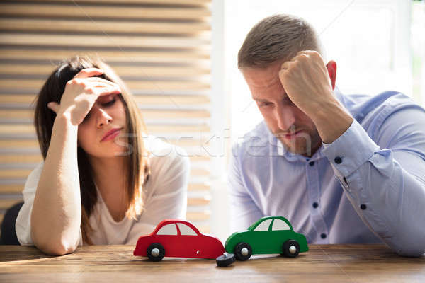 Upset Couple Looking At Car Crash Over Wooden Desk Stock photo © AndreyPopov