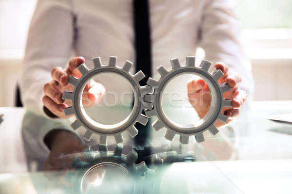 Close-up Of A Person Connecting Two Gears Stock photo © AndreyPopov