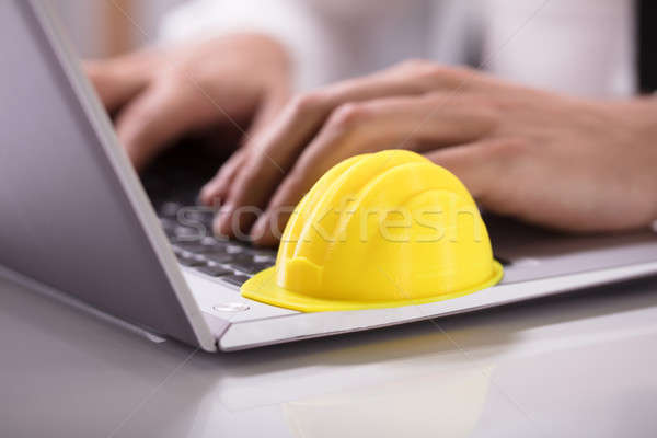 Stock photo: Yellow Hardhat On Laptop Keypad