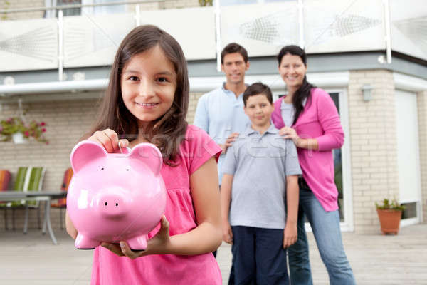 Girl saving money with family at the back Stock photo © AndreyPopov
