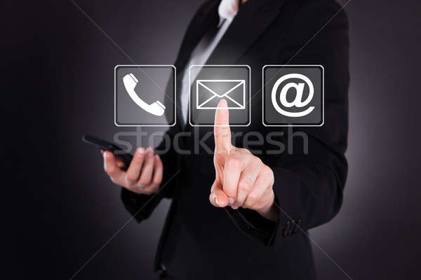 Businesswoman Sending Message Through Smart Phone Stock photo © AndreyPopov