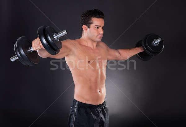 Adam egzersiz dambıl genç kas siyah Stok fotoğraf © AndreyPopov