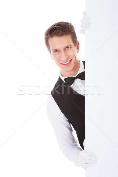 Férfi pincér tart óriásplakát fehér kéz Stock fotó © AndreyPopov