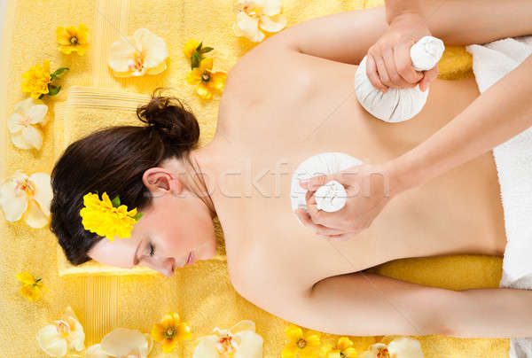 Woman Receiving Massage With Herbal Compress Balls At Spa Stock photo © AndreyPopov