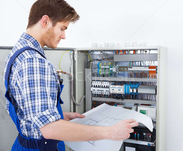 Technician Analyzing Blueprint In Front Of Fusebox Stock photo © AndreyPopov