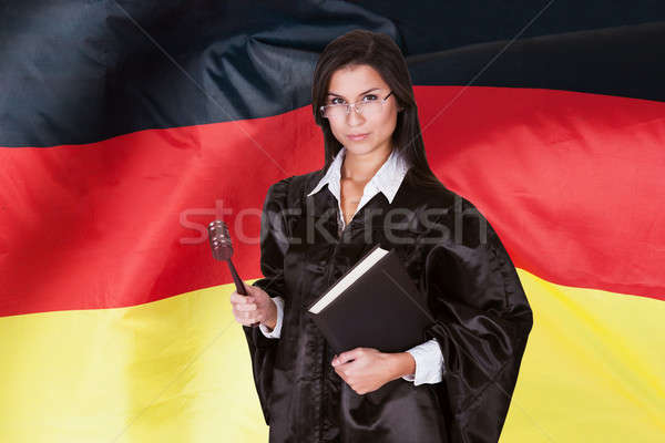 Stock photo: Confident Female Judge With Book And A Wooden Gavel