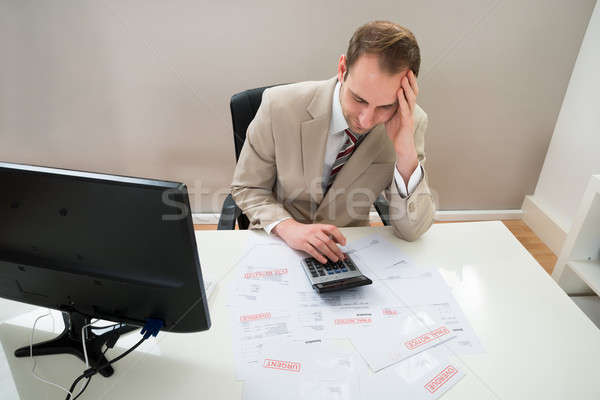 Businessman Calculating Unpaid Bills Stock photo © AndreyPopov