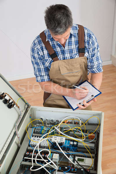 Electrician Looking At Fuse Box Stock photo © AndreyPopov