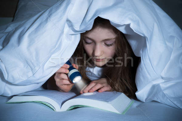 Girl Reading Book With Flashlight Stock photo © AndreyPopov
