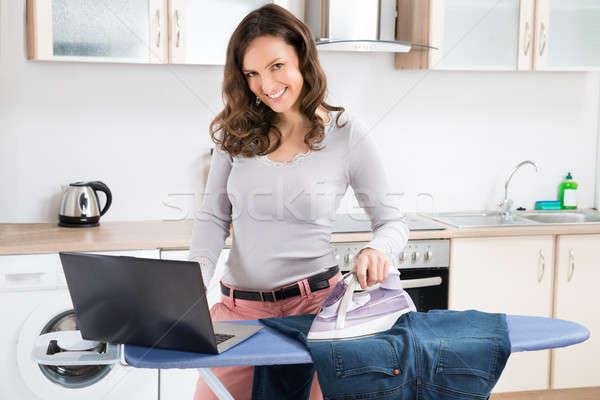 Woman With Laptop While Ironing Jeans Stock photo © AndreyPopov