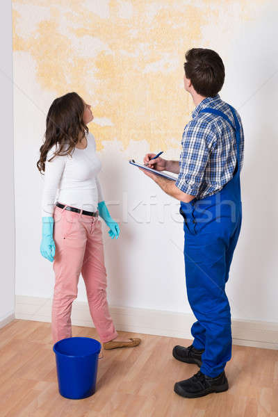 Worker Writing On Clipboard With Woman In House Stock photo © AndreyPopov