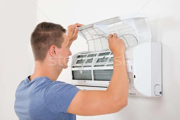 Uomo condizionatore d'aria giovane bianco muro lavoro Foto d'archivio © AndreyPopov