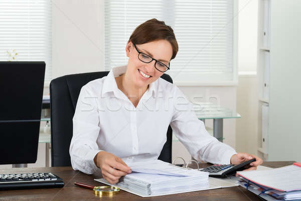 Businesswoman Calculating Tax At Desk Stock photo © AndreyPopov