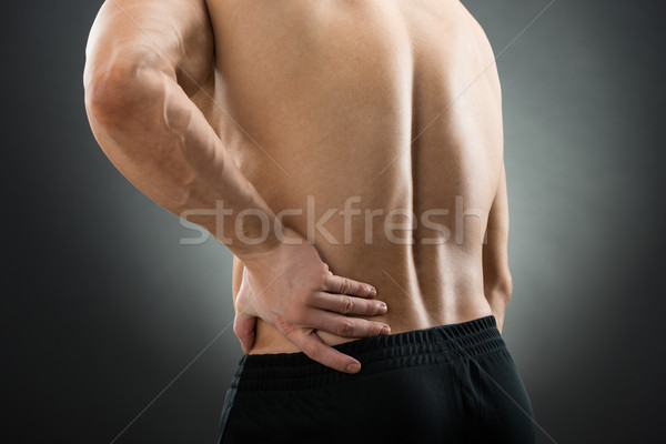 Midsection Of Muscular Man Suffering From Backache Stock photo © AndreyPopov