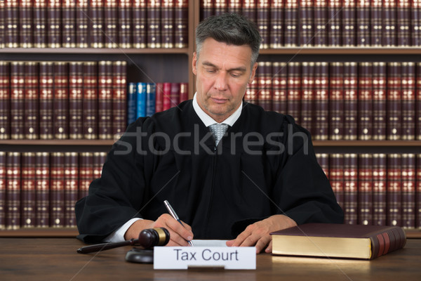 Stock photo: Tax Court Nameplate On Table With Judge Writing In Courtroom