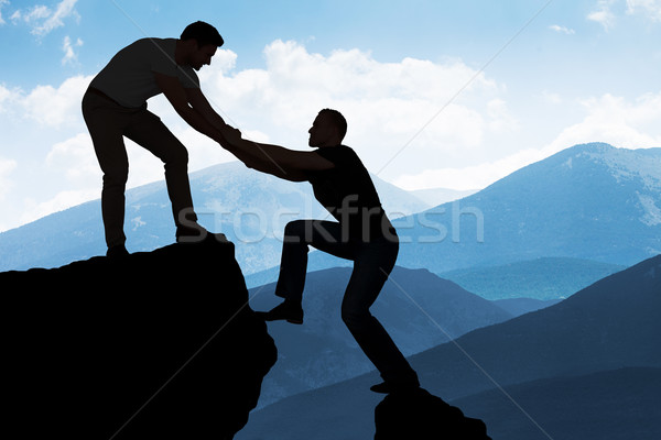 Man Assisting Male Friend In Climbing Rock Stock photo © AndreyPopov