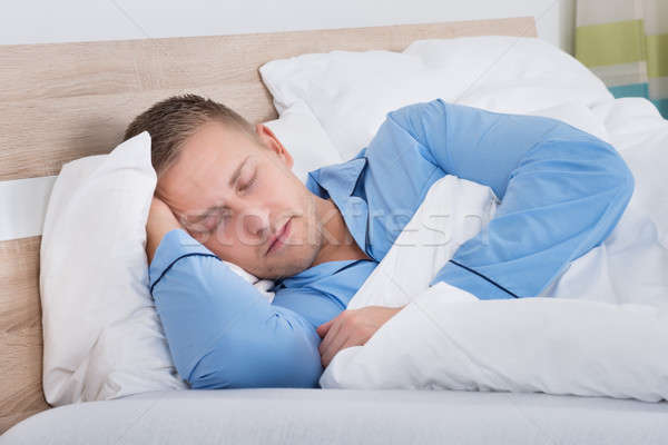 Homem adormecido cama moço quarto casa Foto stock © AndreyPopov