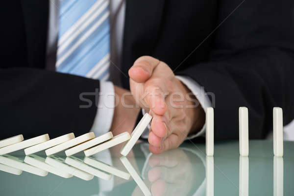 Businessperson Stopping Dominos Falling On Desk Stock photo © AndreyPopov